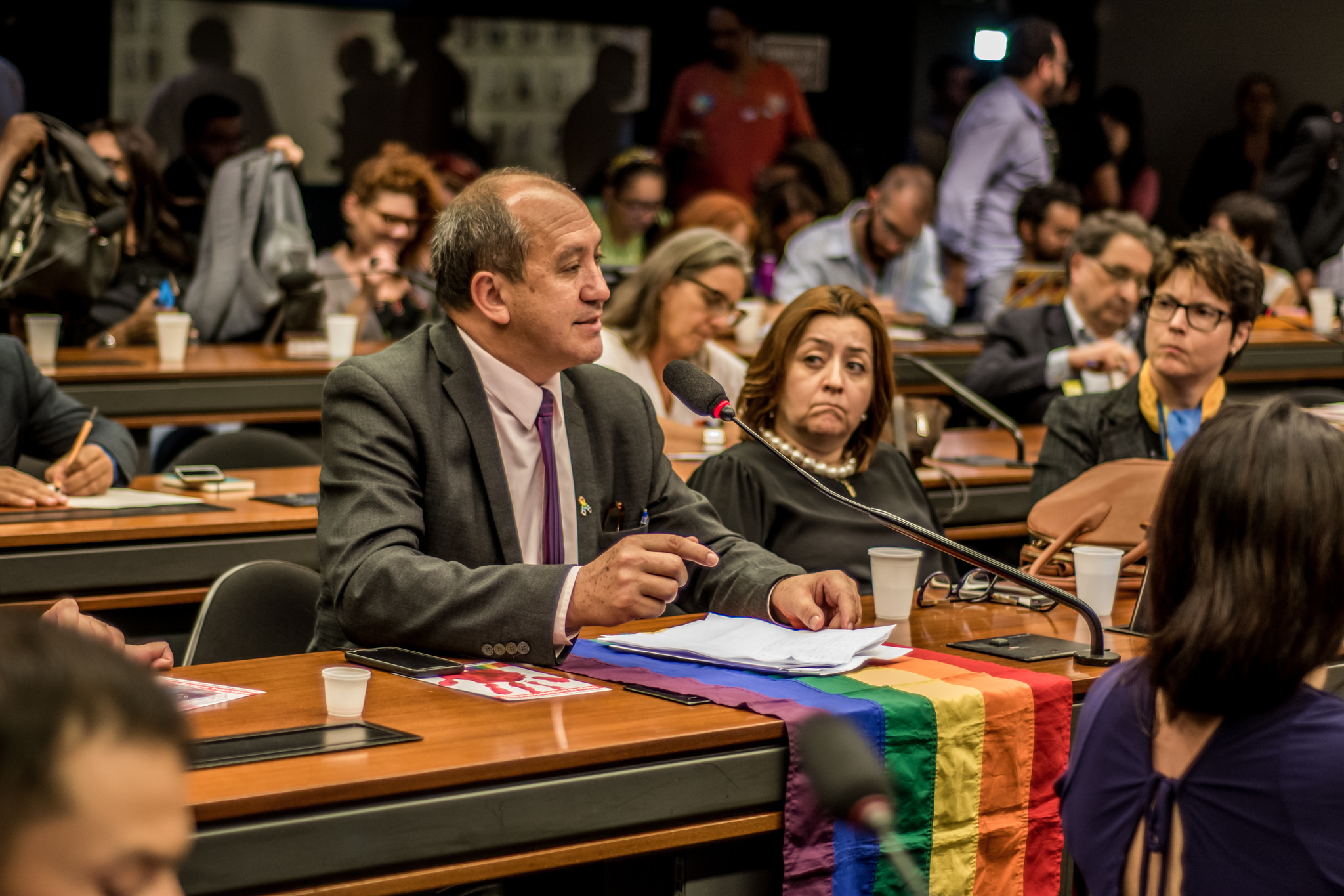 Em foco, Toni Reis, Diretor Presidente da Aliança Nacional LGBTI+. Sobre a mesa está a bandeira LGBTI+.