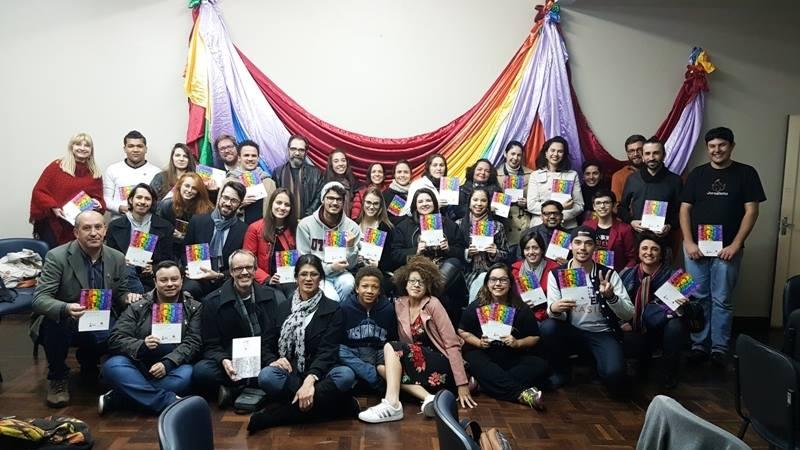 Foto do Lançamento do Manual de Comunicação LGBTI+ na cidade de Curitiba, na sede do Sindicato dos Jornalistas do Paraná. Todos posando para a foto com um exemplar manual em mãos e ao fundo uma bandeira colorida.